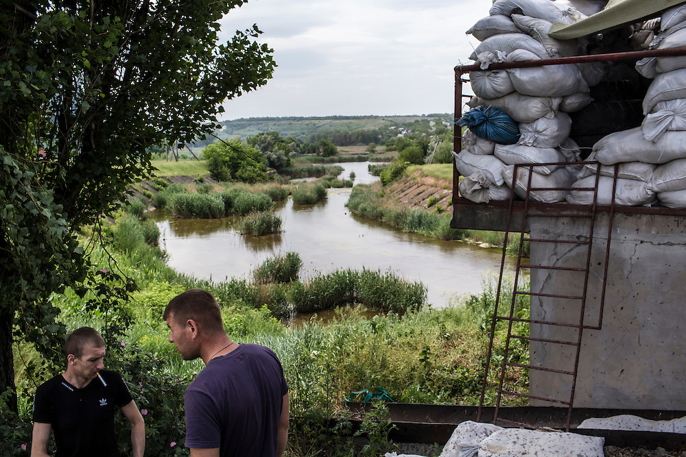 KARLIVKA, UKRAINE - MAY 23: Men look at a deserted checkpoint, which was the scene of an early morning firefight between the pro-Ukraine Donbass Battalion and the pro-Russia Vostok Battalion militias on May 23, 2014 in Karlivka, Ukraine. At least eight people between the two sides, including one civilian, were killed in an early morning firefight when the Donbass Battalion, a pro-Ukraine militia, attacked a Vostok Battalion checkpoint in the nearby town of Karlivka. (Photo by Brendan Hoffman/Getty Images) *** Local Caption ***