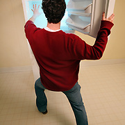 A man reaches into a freezer while smoke pours out of the appliance.
