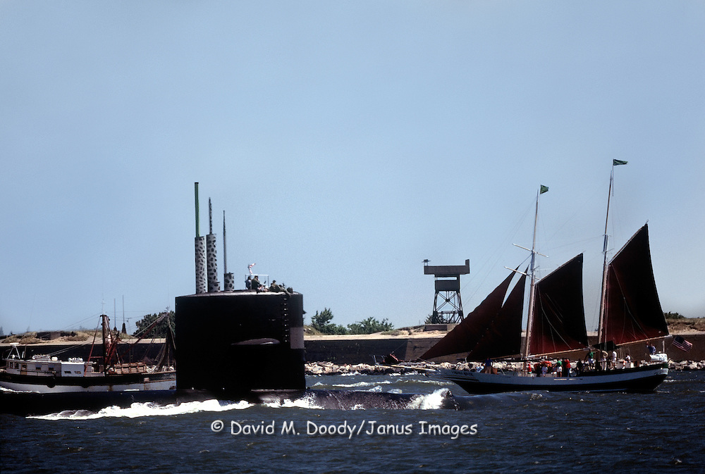 A Nuclear submarine passes the harbor entrance with Fort Wool in the background and the Virginia Rover,  a sightseeing boat and a commercial fishing boat behind the sub. Norfolk- Newport News area (Hampton Roads), Virginia. This harbor entrance is at the southern end of the Chesapeake Bay where the James River empties into the Atlantic Ocean.