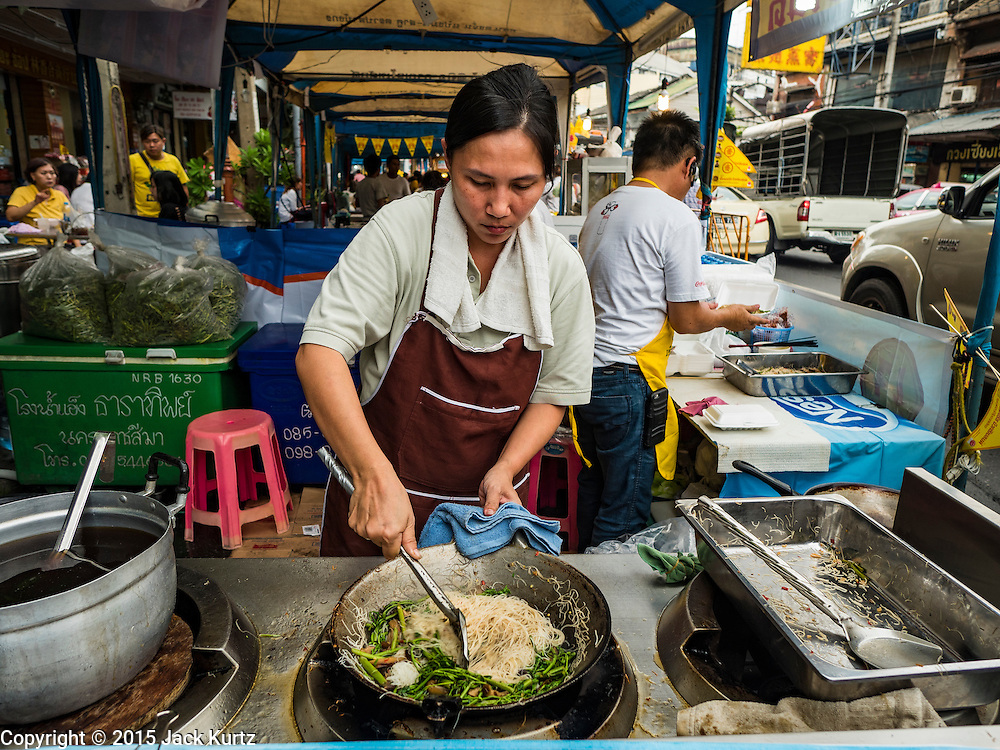 12 OCTOBER 2015 - BANGKOK, THAILAND:  A vendor fries up an order of noodles in a wok on the first day of the Vegetarian Festival in Bangkok's Chinatown. The Vegetarian Festival is celebrated throughout Thailand. It is the Thai version of the The Nine Emperor Gods Festival, a nine-day Taoist celebration beginning on the eve of 9th lunar month of the Chinese calendar. During a period of nine days, those who are participating in the festival dress all in white and abstain from eating meat, poultry, seafood, and dairy products. Vendors and proprietors of restaurants indicate that vegetarian food is for sale by putting a yellow flag out with Thai characters for meatless written on it in red.      PHOTO BY JACK KURTZ