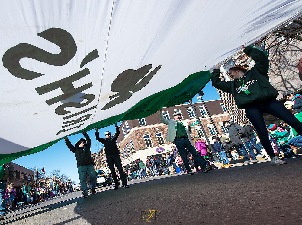 Members of the Irish's Bar float carry a giant Irish flag down the middle of Main Street in Fond du Lac as part of the St. Patrick's Day parade. March 17,  2018, Patrick Flood Photography