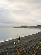 A man fishes from the cobble beach at Kaikoura, Canterbury, New Zealand.