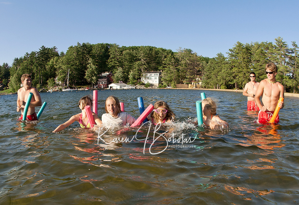 """Cyndal Grant-Vansteensburg, Sydni Lehr, Seanna Langley and Abby Jarvi enjoy """"noodle"""" racing at Gilford Beach during the Kick Off to Summer event put on by Gilford Parks and Recreation Wednesday evening.  (Karen Bobotas/for the Laconia Daily Sun)Gilford Parks and Recreation Summer Kick Off Party at Gilford Beach June 29, 2011."""