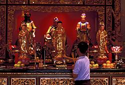 Stock photo of a man lighting incense inside Texas Guandi Buddhist Temple