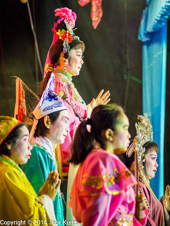 """06 DECEMBER 2015 - BANGKOK, THAILAND: A Chinese opera performance at the Ruby Goddess Shrine in the Dusit district of Bangkok. Chinese opera was once very popular in Thailand, where it is called """"Ngiew."""" It is usually performed in the Teochew language. Millions of Chinese emigrated to Thailand (then Siam) in the 18th and 19th centuries and brought their culture with them. Recently the popularity of ngiew has faded as people turn to performances of opera on DVD or movies. There are about 30 Chinese opera troupes left in Bangkok and its environs. They are especially busy during Chinese New Year and Chinese holidays when they travel from Chinese temple to Chinese temple performing on stages they put up in streets near the temple, sometimes sleeping on hammocks they sling under their stage.     PHOTO BY JACK KURTZ"""