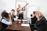 Businessman playing guitar in business meeting