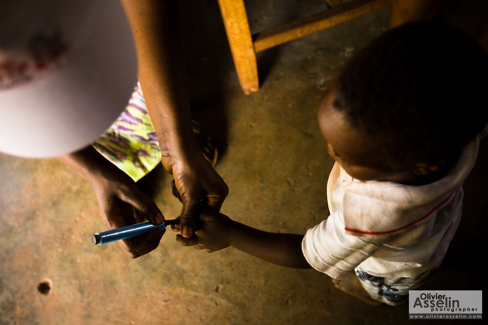 A health worker marks the finger of a child with ink during a national polio immunization exercise at the Moglaa primary school in the town of Moglaa, northern Ghana on Friday March 27, 2009.