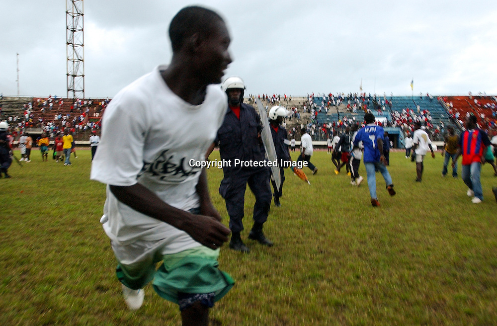As the match finally ends in a 3-0 loss for the home team, fans dart between police on the pitch.