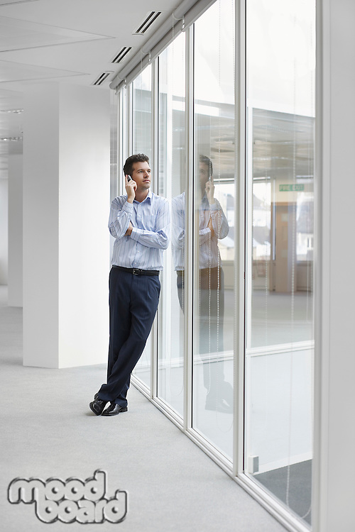 Office worker talking on mobile phone looking out window in empty office space