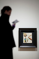 © Licensed to London News Pictures. 28/01/2013. London, UK. A Tate Britain employee reads a guidebook in front of 'Untitled (Heavy Relief)' (1945) by Kurt Scwitters at the press view of an exhibition of the artists work taking place at the Tate Britain in London. The exhibition, 'Schwitters in Britain', is the first to to examine the work of the late German modernist artist's 'British period' (1940-1948), and runs from 30th of January 2013 to the 12th of May 2013. Photo credit: Matt Cetti-Roberts/LNP