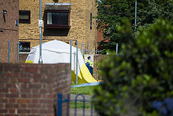 A police officer mans the cordon near the tent marking the spot where a 24 year old male known locally as Mali died at the scene of yet another murder, this time on an estate on Crows Road in Barking, London, May 18 2018.