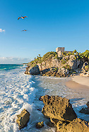 Pelicans soar past the ancient Mayan ruins at the Tulum Archeological Site in Tulum, Mexico.