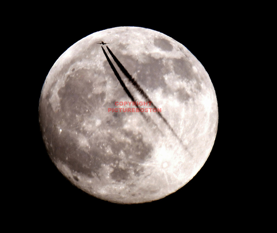 A nearly full moon is accentuated by a high altitude jet entering the east coast of Massachusetts.......