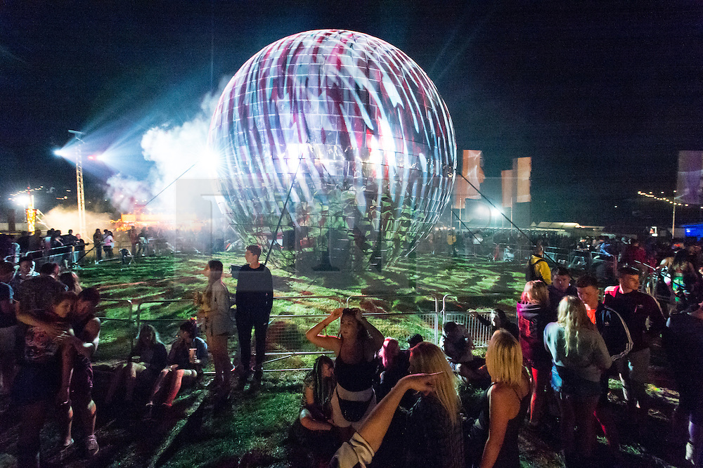 © Licensed to London News Pictures. 04/09/2014. Isle of Wight, UK. Festival goers enjoy the nighttime music and DJ's amongst alongside a giant glitter ball  at Bestival 2014 Day 1.  Bestival organisers claim the glitter ball to be the largest in the world and Guinness World Records officials will arrive to judge this.  Disco legend Chic (featuring Nile Rodgers) will be performing as Sunday night headliner to close the festival.   The weather has been warm and sunny. Photo credit : Richard Isaac/LNP
