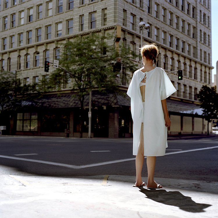 30 something woman in medical gown standing on urban street corner.