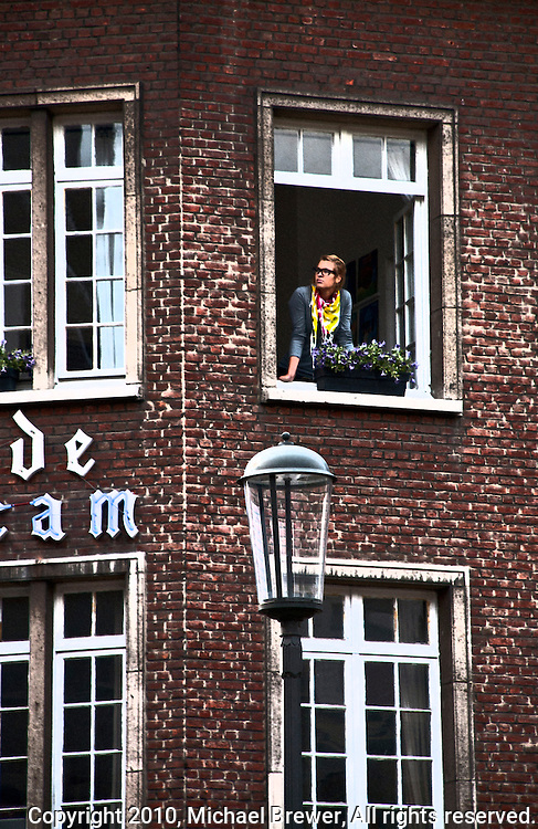 Woman staring out the window of a brick building in Antwerp, Belgium