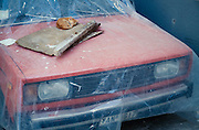 Cat having a nap on a Lada covered with a plastic sheet.