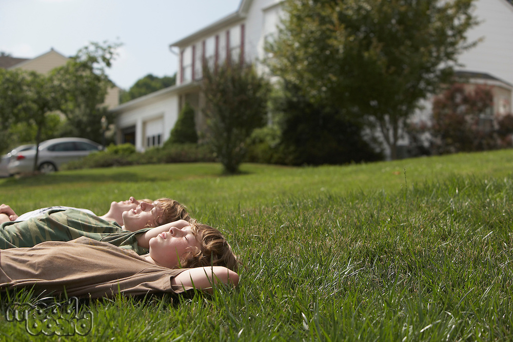 Three teenage brothers (13-17) lying down on front lawn side view