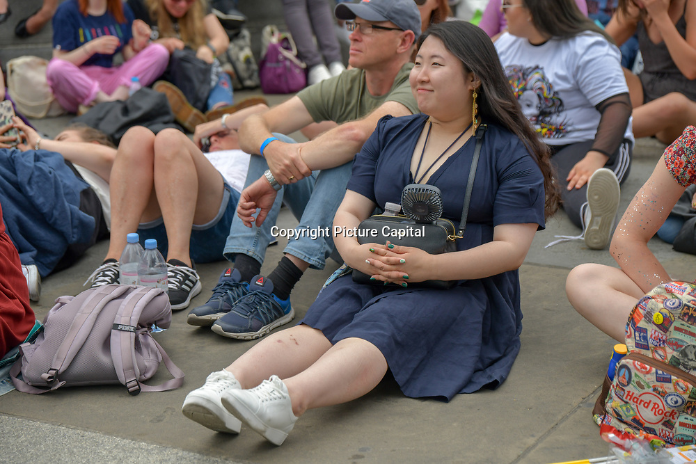 An Asian lady sitting comfordly with an mini fan watching West End Live 2019 - Day 2 in Trafalgar Square, on 23 June 2019, London, UK.