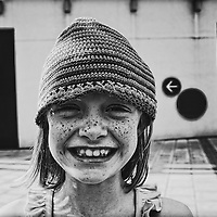 A girl with freckles and a hat smiling