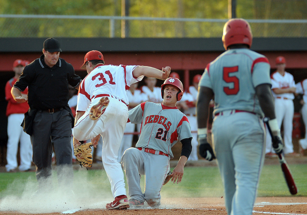 Harrison Central's Chris Wease (21) slides safely past home base as Petal's pitcher Larson Barkurn (31) attempts to tag him out on Friday during their playoff game at Petal. Bryant Hawkins/The Hattiesburg American
