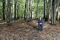 Portrait of business man sitting on office chair in middle of forest