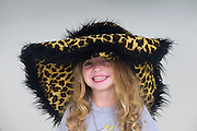 Smiling young girl of three with leopard fur hat