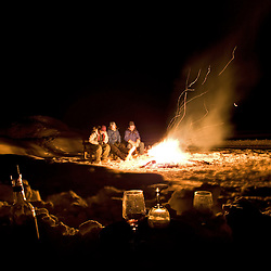People sit around a bonfire with a glass of wine and marshmellows at night in the arctic circle, at Bettles, Alaska.