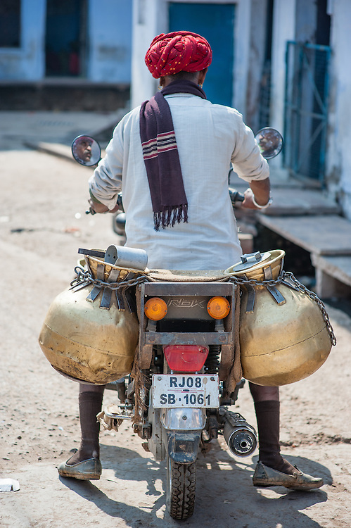Man carrying jars in a motorbike (India)