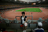 """A Chinese spectator poses for a snapshot inside the National Stadium, also known as the """"Bird's nest"""" in Beijing , China, Saturday, Aug.16, 2008. It is one of the strangest things about the Olympics: From far away, it looks very close. Watching the Olympics on television, the athletes are right in front of you.  Up close, though, it's normally a different story. From the spectators' stands, the athletes are often just distant specks amid the enormity of some of the largest sports stadiums in the world. (Elizabeth Dalziel)"""
