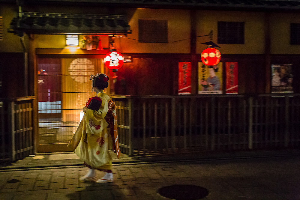 A geiko (as geisha are referred to in Kyoto) passes near a teahouse in Hanami Koji.