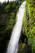 A hiker behind Tunnel Falls along the Eagle Creek trail in the Columbia Gorge area of Oregon.