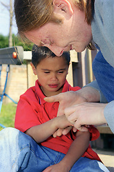 Father examining young son's injured hand in children's playground,