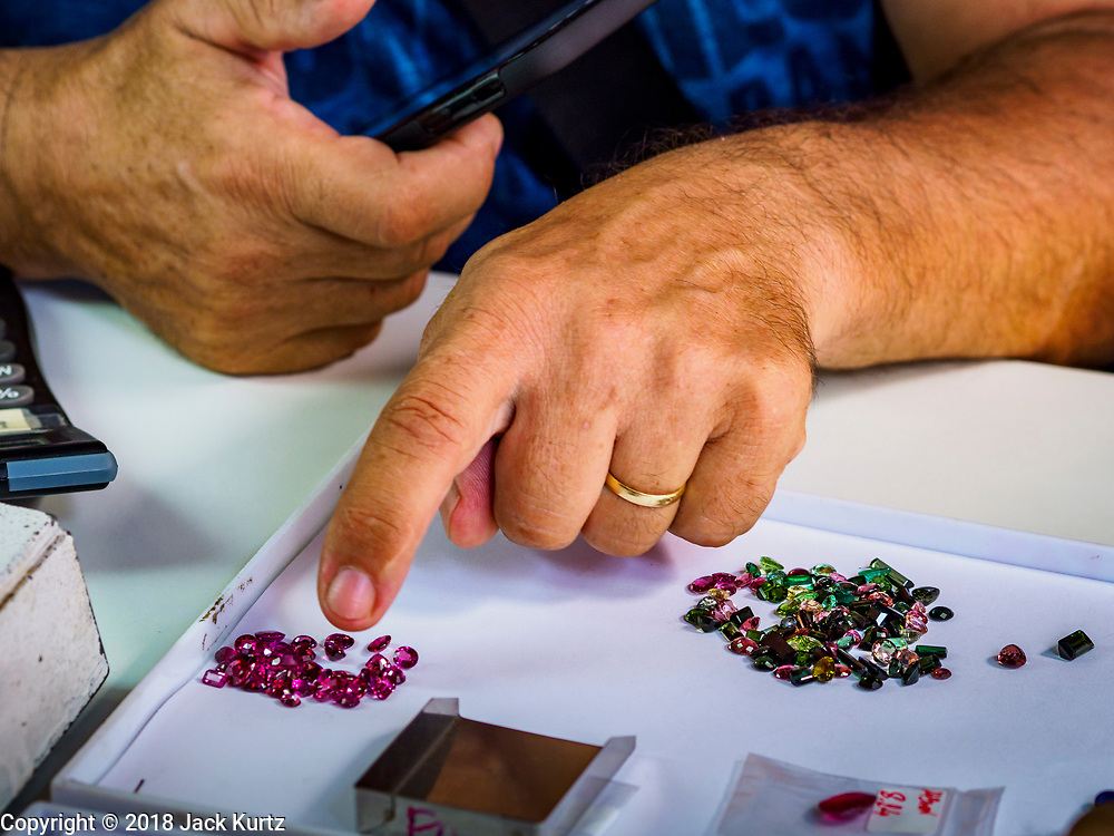 22 DECEMBER 2018 - CHANTABURI, THAILAND: A European gem buyer looks at gems brought to him in the gem market in Chantaburi. The gem market in Chantaburi, a provincial town in eastern Thailand, is open on weekends. Chantaburi used to be an active gem mining area in Thailand, but the mines are played out now. Now buyers and sellers come from around the world to Chantaburi for the weekend market. Many of the stones come from Myanmar, others come from mines in Afghanistan and Africa.     PHOTO BY JACK KURTZ