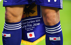 Captain Makoto Hasebe of Japan holds the pennant during the national anthems that was later presented to opponents Qatar