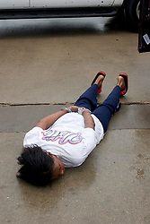24 Sept, 2005.  Beaumont, Texas. Hurricane Rita. <br /> <br /> Police from the Beaumont rapid reaction force arrest looters who they captured breaking into a Chevron petrol station just off interstate 10. Evette Riley (31yrs) lies face down on the concrete and said, 'I guess it wasn't a very smart thing to do.' when all they had taken was a few cartons of cigarettes and some sodas.<br /> Photo; ©Charlie Varley/varleypix.com