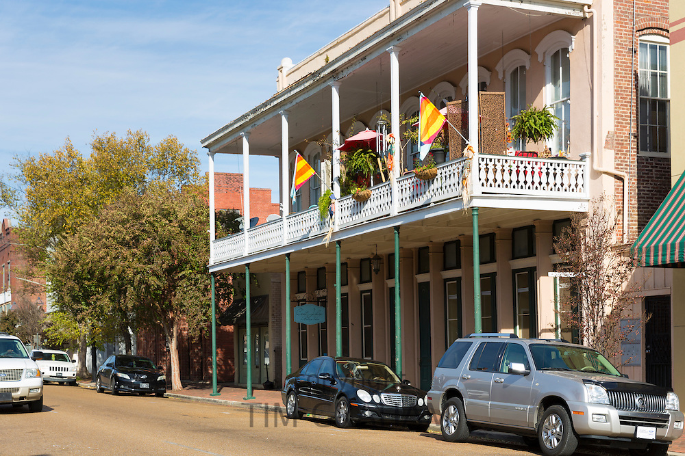 Shops, traditional balcony and parked autos in Main Street, Downtown Natchez, Mississippi USA
