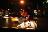 A girl on her father's bike on a cold December evening, Beijing, China.
