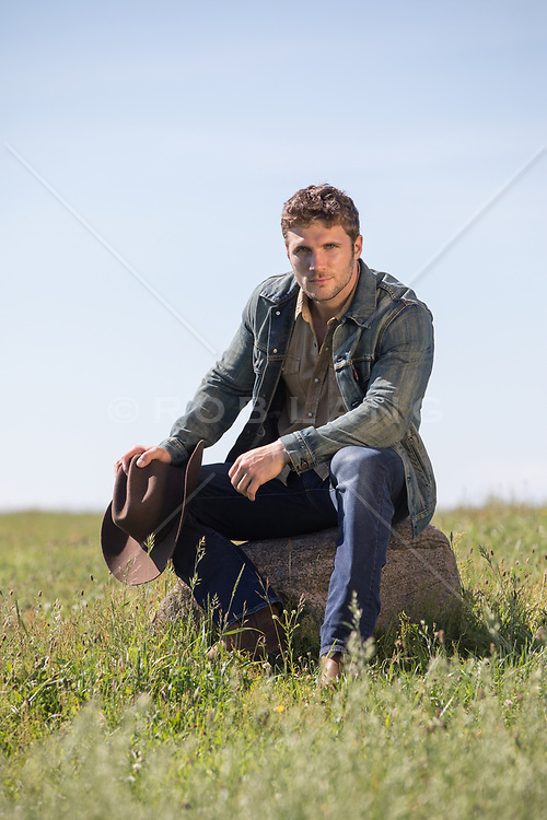 hot cowboy sitting on a rock