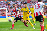 Grant Leadbitter (#23) of Sunderland AFC clears the ball ahead of Callum Reilly (#33) of AFC Wimbledon during the EFL Sky Bet League 1 match between Sunderland and AFC Wimbledon at the Stadium Of Light, Sunderland, England on 24 August 2019.