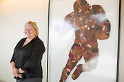 Bay Area artist Jenny Kompolt poses for a portrait with her Running Back piece, which is pieced together entirely out of worn footballs, during the Levi's Stadium Art Collection grand opening event at Levi's Stadium in Santa Clara, California, on August 1, 2014. (Stan Olszewski/SOSKIphoto for Content Magazine)