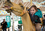 Sophia on the carousel in City Park while her mother looks on; New Orleans, Louisiana