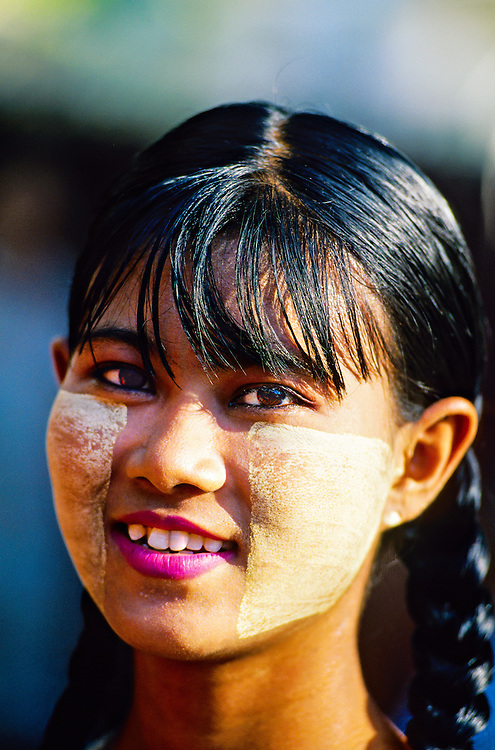 Burmese woman with thanaka bark makeup outside Shwe Nandaw Kyaung Monastery, Mandalay, Burma (Myanmar)