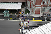 corner south exit Tokyo Station with pedestrians and school group and zebra crossing Japan