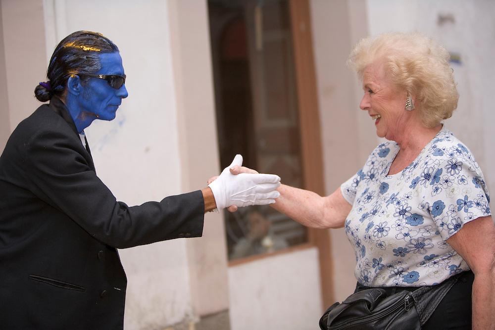 "Elderly woman with ""blue man"" street performer, Cuenca, Ecuador, South America"