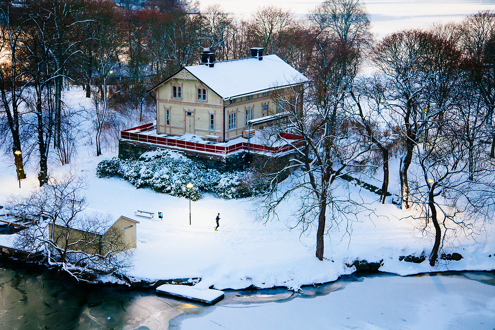 A runner running through a snow covered Rålambhovspark in Kungsholmen, Stockholm.  The park is well lit by the many streetlamps that illuminate the running path.  The frozen lake Mälaren is visible in the foreground.