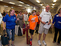 """John Walker (on right) organizes volunteers as they pack up """"Got Lunch"""" bags for delivery to approximately 240 homes on Day 1 of the summer program.  (Karen Bobotas/for the Laconia Daily Sun)"""