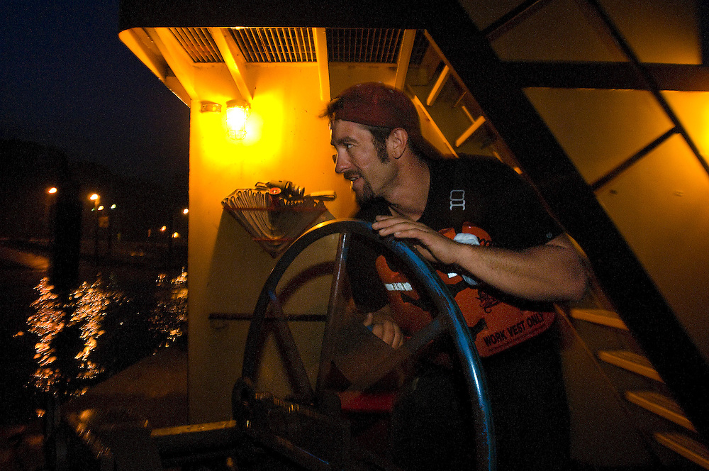 Trumbull River Service towboat deckhand Bill Beard tightens a cable while working in the darkness of the Illinois River at night. ©David Zalaznik