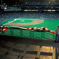 USA, Washington, Baseball fan watches Seattle Mariners' home opener at sunset from Safeco Field's upper decks