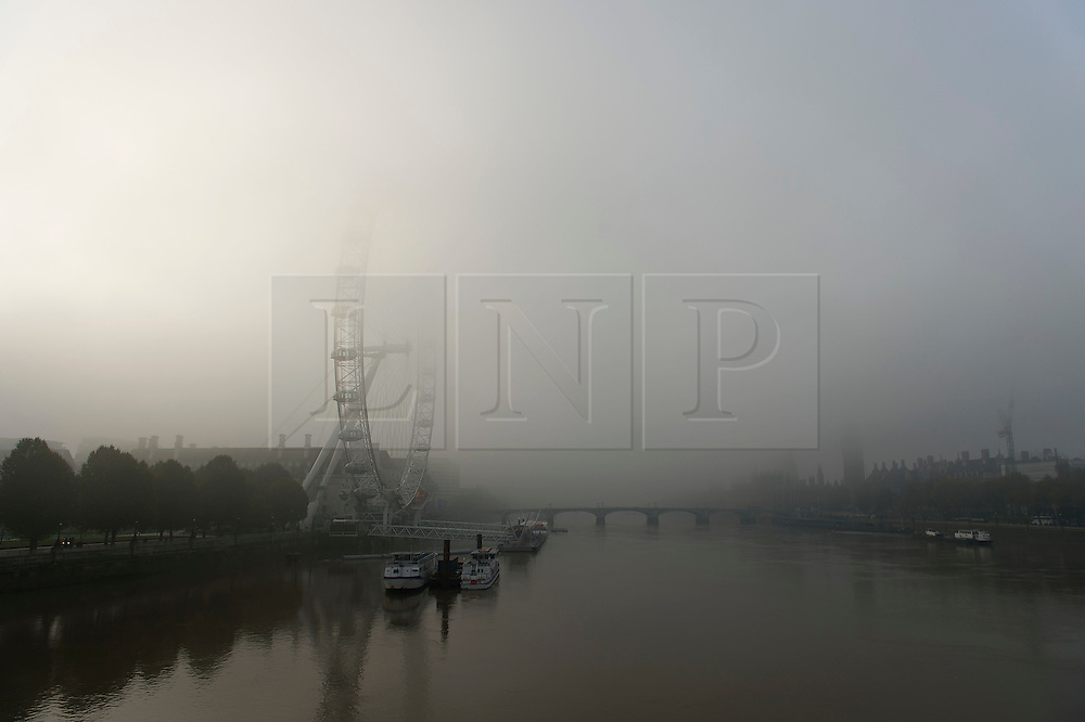 © Licensed to London News Pictures. 01/11/2015. London, UK.  Fog covering the London Eye and Houses of Parliament next to the River Thames in Westminster on an early autumn morning.  Photo credit: Ben Cawthra/LNP